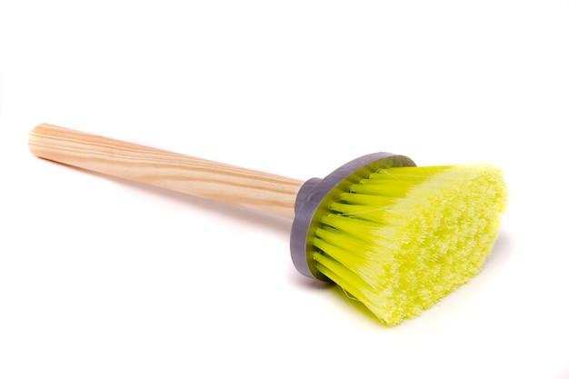 Feche acima da vista de uma escova pequena da poeira com o punho de madeira isolado em um fundo branco.
