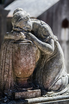 Feche acima da vista de uma estátua de um túmulo no famoso cemitério português prazeres em lisboa, portugal.