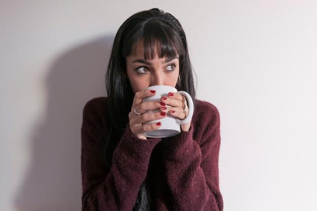 Feche acima da vista de uma jovem mulher bonita bebendo uma xícara de chá ou café em casa. relaxe em ambientes fechados