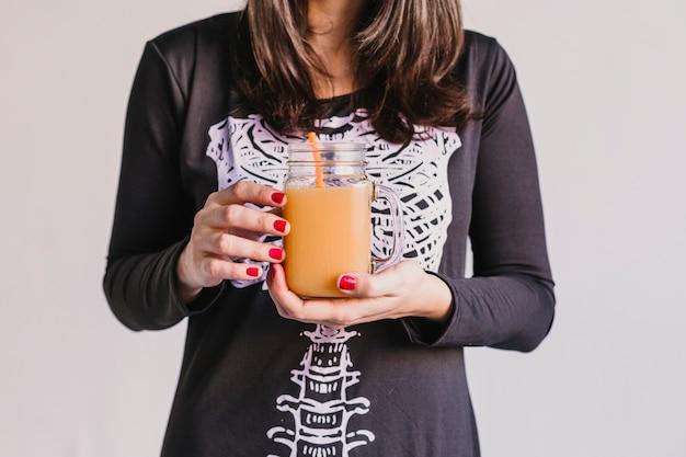 Feche acima da vista de uma jovem mulher bonita segurando suco de laranja. vestindo uma fantasia de esqueleto preto e branco. conceito de dia das bruxas. interior