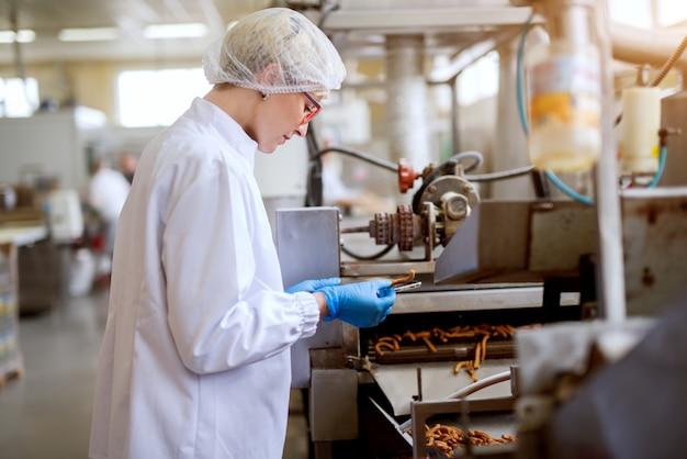 Feche acima da vista de uma jovem trabalhadora preocupada em panos estéreis, inspecionando palitos de sal retirados da linha de produção de lanches de alimentos.