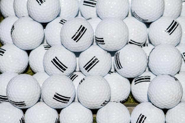 Feche acima da vista de uma pilha das bolas de golfe brancas.