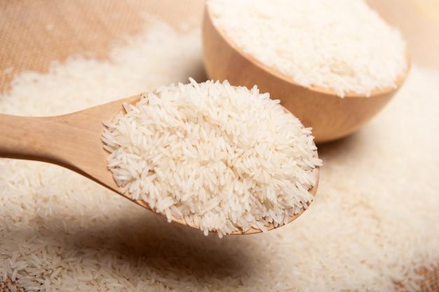 Feche acima da vista do arroz em uma colher e em uma bacia de madeira no conceito de madeira do fundo, o orgânico e o saudável.