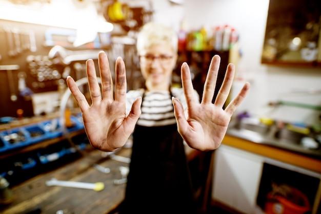 Feche acima da vista do foco da mulher profissional trabalhador que guarda as mãos sujas.