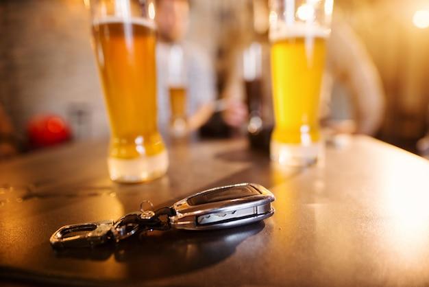 Feche acima da vista do foco das chaves do carro na mesa da barra na frente dos vidros com cerveja de pressão.