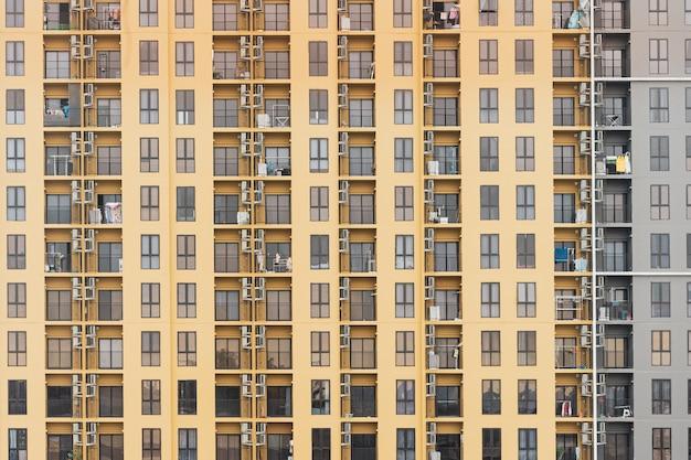 Feche acima da vista do prédio de apartamentos alto do condomínio em tailândia com geometria e detalhe fortes.