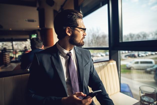 Feche acima da vista lateral do barbudo bonito jovem empresário elegante terno sentado em um café no andar de cima e olhando para longe enquanto segura um móvel.