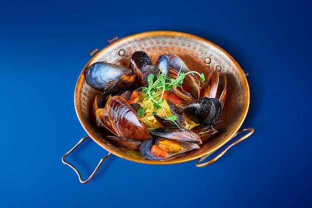 Feche acima da vista na bacia saboroso com mexilhões nas conchas. aperitivo delicioso de frutos do mar