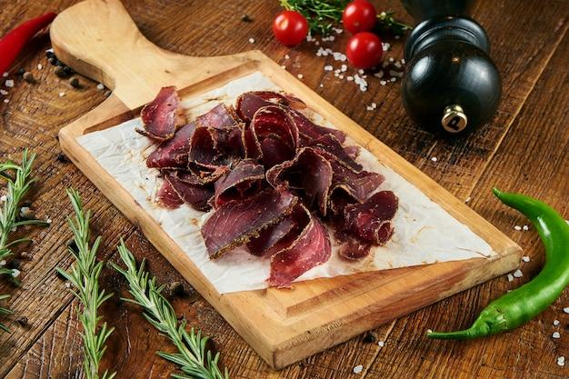 Feche acima da vista na carne de vaca seca cortada saboroso no pergaminho em uma placa de madeira em uma superfície de madeira em uma composição com especiarias. lanche de cerveja. pastärma