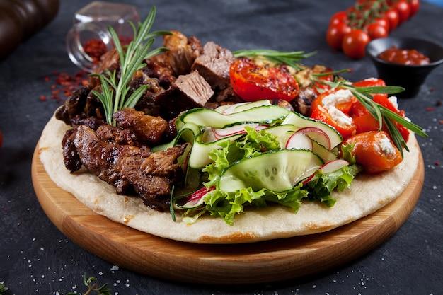 Feche acima da vista na carne grelhada saboroso com os vegetais no pão árabe georgiano. shashlik ou carne de churrasco na pita. shish kebab, comida tradicional da cozinha georgiana.