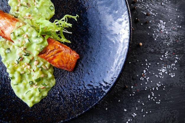 Feche acima da vista no bife de salmão no prato escuro facture servido com molho verde. foco seletivo na farinha de peixe. bife de salmão cozido para um jantar saudável.