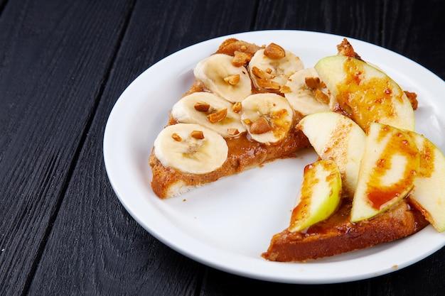 Feche acima da vista no brinde doce do café da manhã com banana e maçã derramada com caramelo no fundo escuro com espaço da cópia. refeição de sanduíche. comida para o café da manhã.