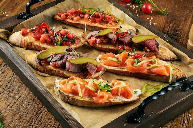 Feche acima da vista no bruschetta delicioso sortido com salmão, carne e tomate na superfície de madeira. aperitivo italiano. antipasti.
