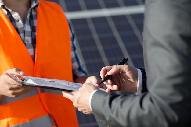 Feche acima da vista no contrato sigining do contramestre e do cliente na central eléctrica solar.