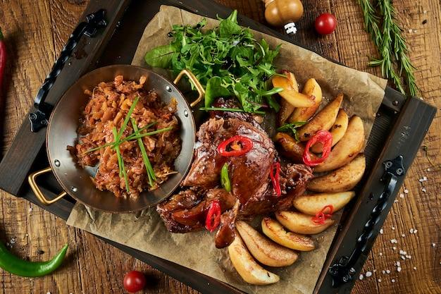 Feche acima da vista no filé de pato cozido saboroso com batata e couve e pimentão em uma superfície de madeira. carne saborosa para um jantar festivo. vista superior plana leigos