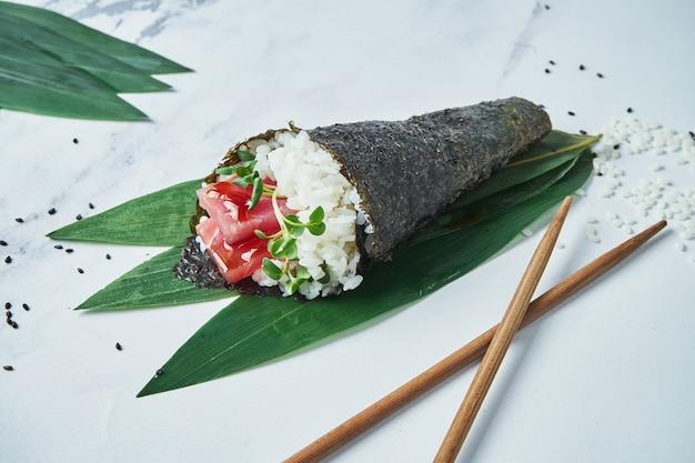 Feche acima da vista no fresco, sushi do temaki do marisco com atum na superfície branca. rolo de mão tradicional. foco seletivo e horizontal