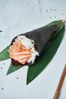 Feche acima da vista no fresco, sushi do temaki do marisco com salmões no branco.