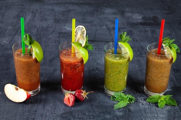 Feche acima da vista no grupo diferente de batido no fundo escuro. smoothies de frutas e vegetais frescos saudáveis com ingredientes variados em vidro.