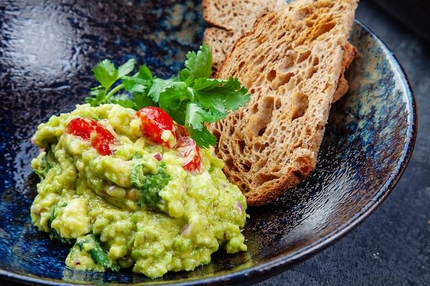 Feche acima da vista no guacamole tradicional de abacate com salsa e tomate cereja, pão servido na tigela escura. cozinha mexicana. lanche para o almoço. fundo de alimentos. foto para o menu