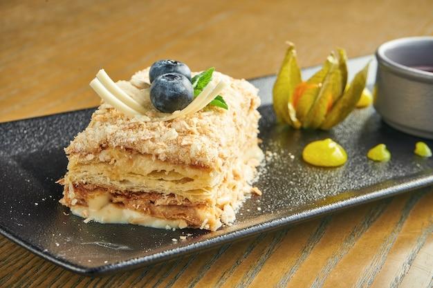 Feche acima da vista no pedaço de bolo napoleon com o morango na placa cerâmica na parede de madeira. cozinha russa, bolo em várias camadas com creme de confeiteiro. foco seletivo