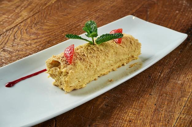 Feche acima da vista no pedaço de bolo napoleon com o morango na placa cerâmica na superfície de madeira. cozinha russa, bolo em várias camadas com creme de confeiteiro. foco seletivo