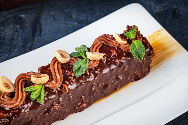 Feche acima da vista no saboroso bolo marrom com porca e chocolate. sobremesa servida em fundo escuro, com espaço de cópia. imagem para menu ou receita.