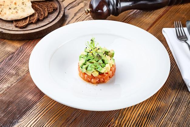 Feche acima da vista no tartare de salmão fresco com abacate e microgreen na placa branca. tartare caseiro em fundo de madeira com espaço de cópia. comida servida para menu ou receita. lanche de cozinha italiana