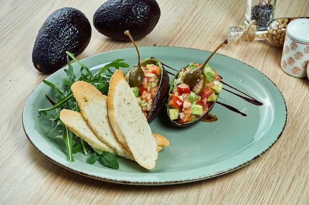 Feche acima da vista no tartare de salmão servido com pão, molho e salsa na placa cerâmica azul. peixe tartare plano leigos.