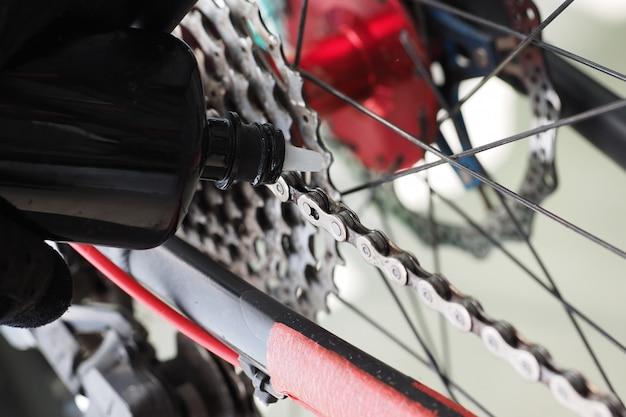 Feche acima da vista. o motociclista da montanha lubrifica a corrente de bicicleta.