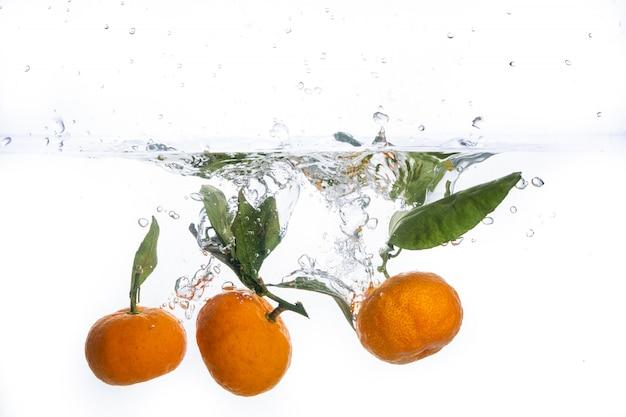 Feche acima da vista que espirra a água e o mandarino.