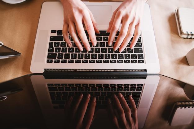 Feche acima da vista superior da mulher de negócios moderna, digitando em um teclado de laptop com reflexo na tela.