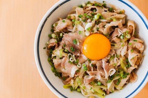 Feche acima da vista superior de butadon: prato japonês da bacia de arroz que consiste na carne de porco e na cebola.