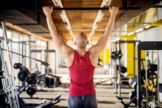 Feche acima da vista traseira do motivado e focado forte muscular ativo saudável careca jovem trabalho pull ups no ginásio moderno.