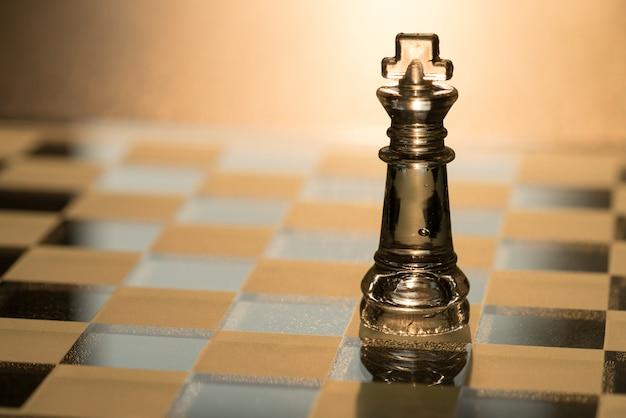 Feche acima da xadrez de cristal do rei na placa de xadrez com fundo da luz solar.