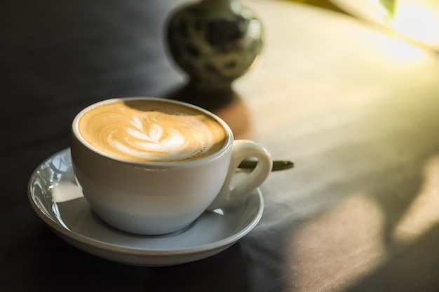Feche acima da xícara branca do café quente com leite com arte de espuma de leite com placa e colher na mesa de madeira com luz solar.