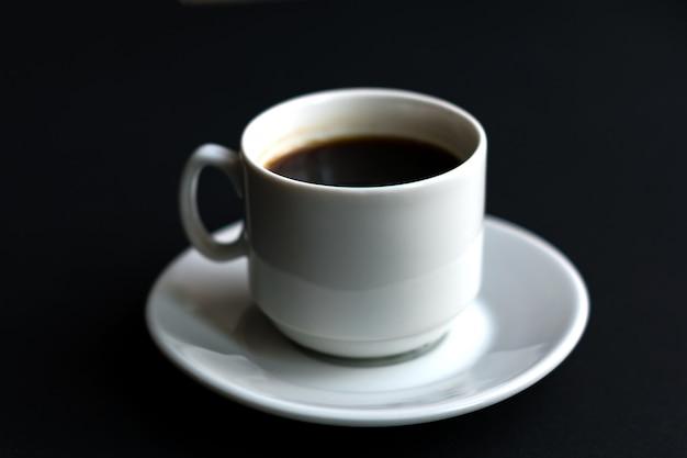 Feche acima da xícara de café branca no fundo preto. foco suave
