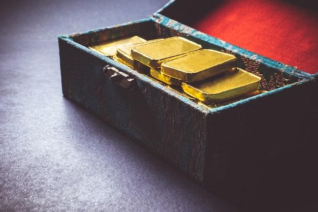 Feche acima das barras de ouro puras na caixa no fundo escuro.