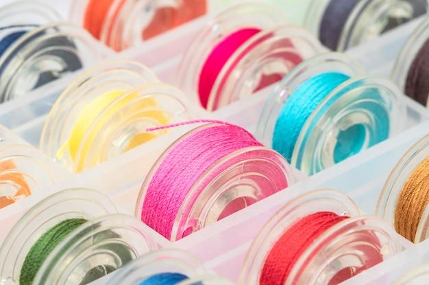Feche acima das bobinas plásticas da máquina de costura com a linha colorida na caixa plástica.