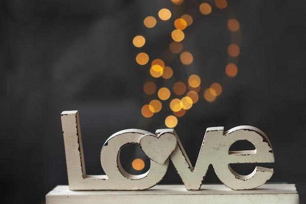 Feche acima das cartas de amor de madeira da foto no fundo do bokeh.