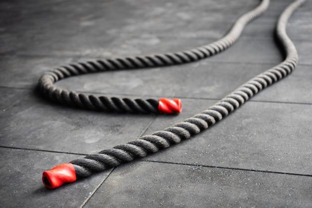 Feche acima das cordas de batalha da aptidão mentem no assoalho preto no gym da aptidão.