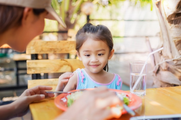 Feche acima das crianças tailandesas que comem no restaurante com sua mãe