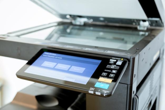 Feche acima das folhas de papel na impressora na sala do escritório.