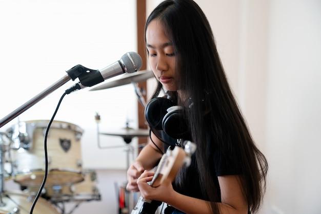 Feche acima das imagens da menina que jogam a guitarra.