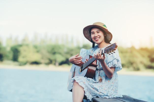 Feche acima das imagens das mãos da mulher que jogam a guitarra acústica