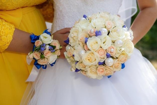 Feche acima das mãos com o ramalhete da noiva e da dama de honra de rosas bege.