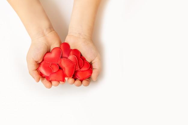 Feche acima das mãos da criança que guardam o coração vermelho no fundo branco - conceito dos povos, do amor, da caridade e de família