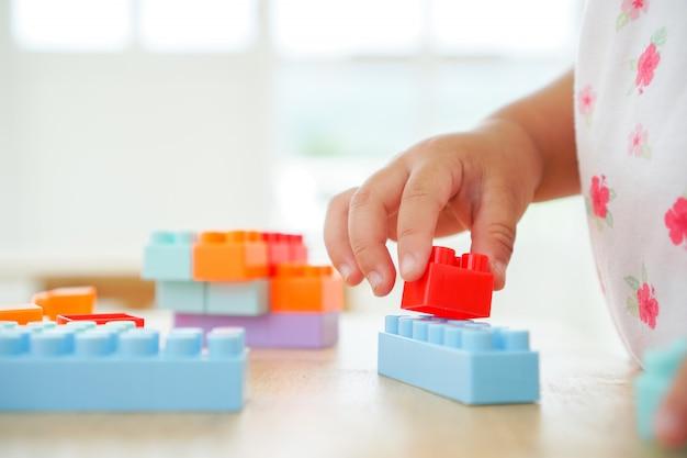 Feche acima das mãos da criança que jogam com os brinquedos coloridos do conector na tabela. brinquedos educativos para criança pré-escolar e jardim de infância.