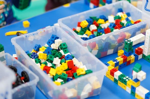 Feche acima das mãos da criança que jogam com os tijolos plásticos coloridos na tabela.