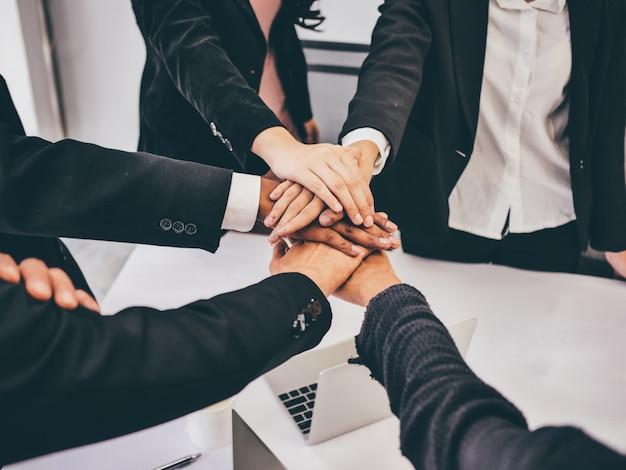 Feche acima das mãos da equipe do negócio na sala de reunião, conceito dos trabalhos de equipa.