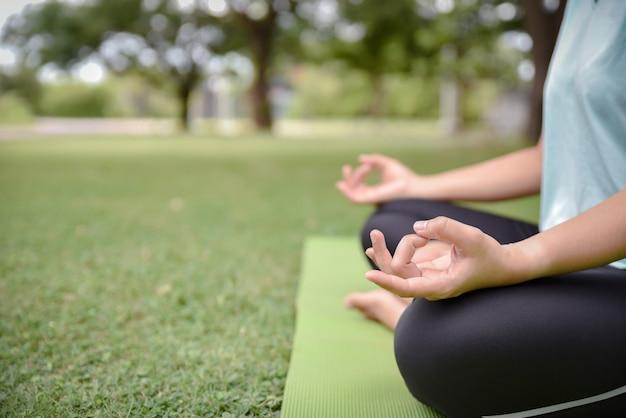 Feche acima das mãos da mulher fazem a ioga ao ar livre no parque.